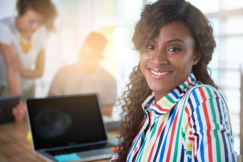 Imagen de una mujer de negocios casual acertada que usa el ordenador portátil durante la reunión foto de archivo libre de regalías