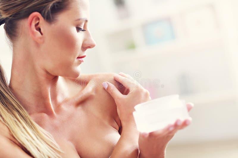 Imagen de una mujer del ajuste que sostiene la loción sobre su cuerpo fotos de archivo libres de regalías