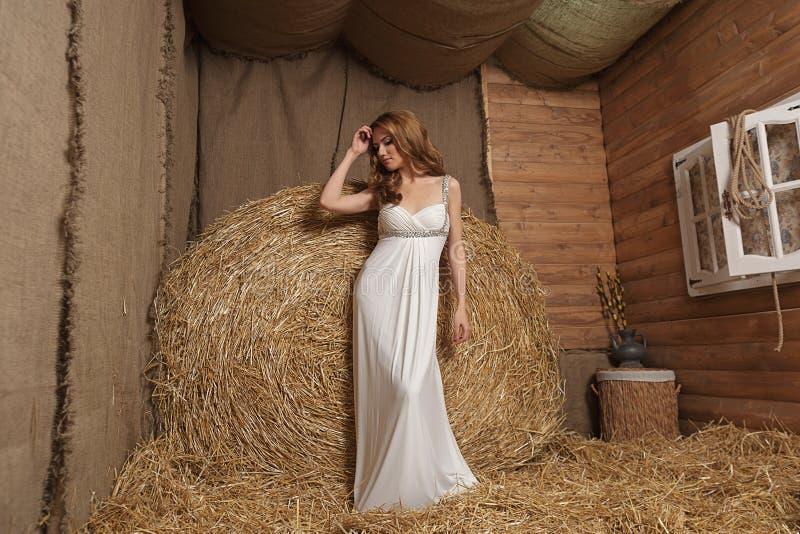 Imagen de una mujer joven atractiva con el pelo rojo largo en un vestido de boda en un henil fotografía de archivo