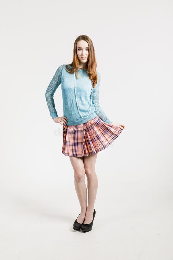 Imagen de una mujer joven que lleva una falda corta y un jersey de la turquesa fotografía de archivo libre de regalías