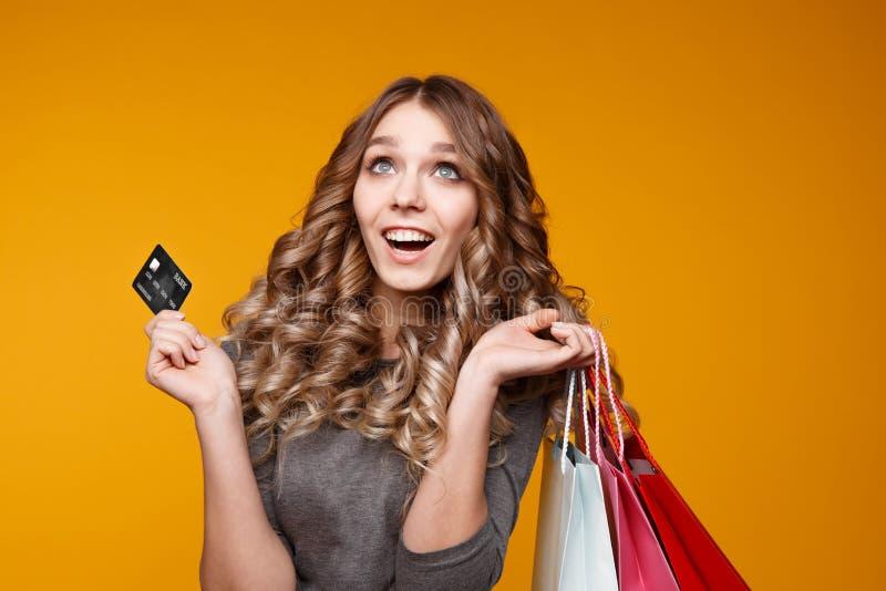 Imagen de una mujer morena joven alegre en el vestido blanco del verano que sostiene la tarjeta de crédito que presenta con los b fotos de archivo