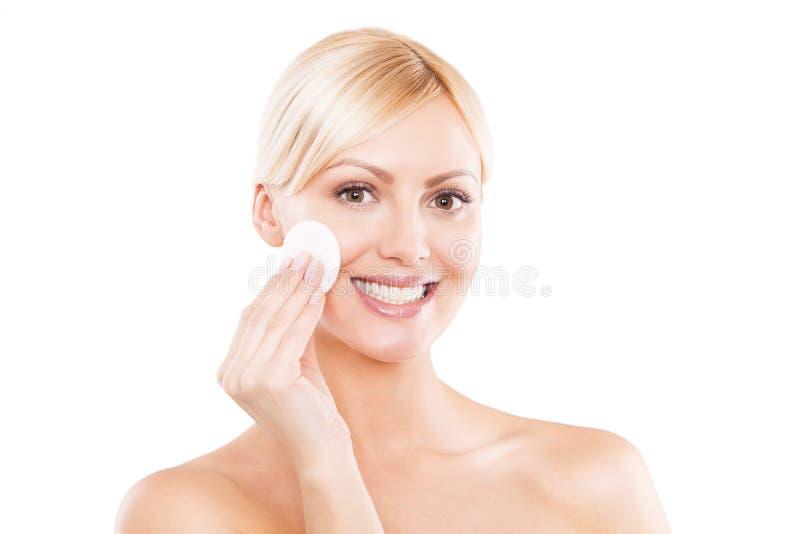 Imagen de una mujer rubia feliz que limpia su cara fotografía de archivo