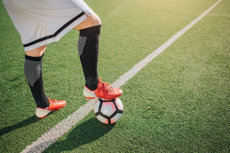 Imagen de una parte más inferior del futbolista del cuerpo Él se coloca en la pierna verde del campo y del control uno en bola La foto de archivo