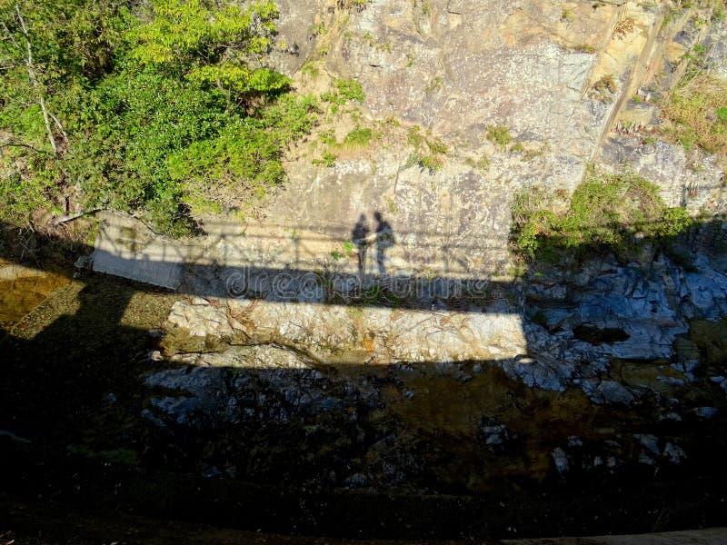 Imagen de una sombra de dos personas que caminan en un puente de acero suspendido en Kobe, Japón imagenes de archivo