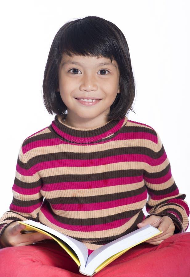 Imagen de una sonrisa de la niña que celebra un libro en el fondo blanco foto de archivo