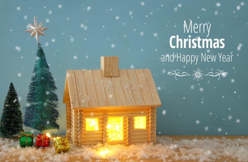 Imagen del árbol de navidad y de la casa de madera con la luz a través de la ventana, sobre la tabla nevosa fotos de archivo