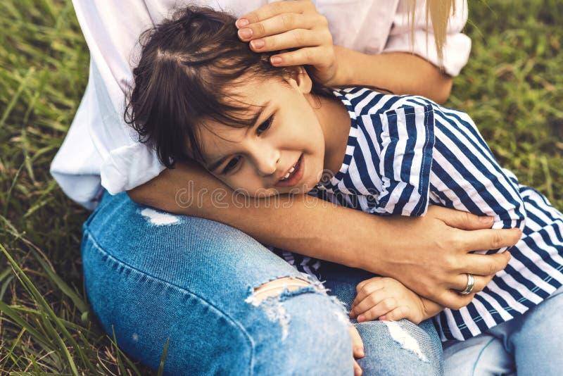 Imagen del abrazo lindo feliz y de la mentira de la niña en sus piernas de la madre al aire libre Madre e hija de amor que asiste imagen de archivo libre de regalías