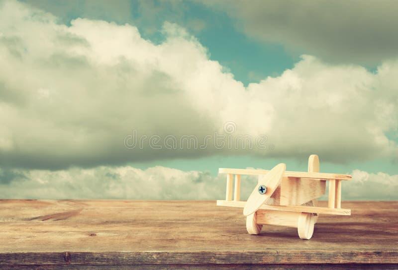 Imagen del aeroplano de madera del juguete sobre la tabla de madera contra el cielo nublado Imagen retra del estilo foto de archivo