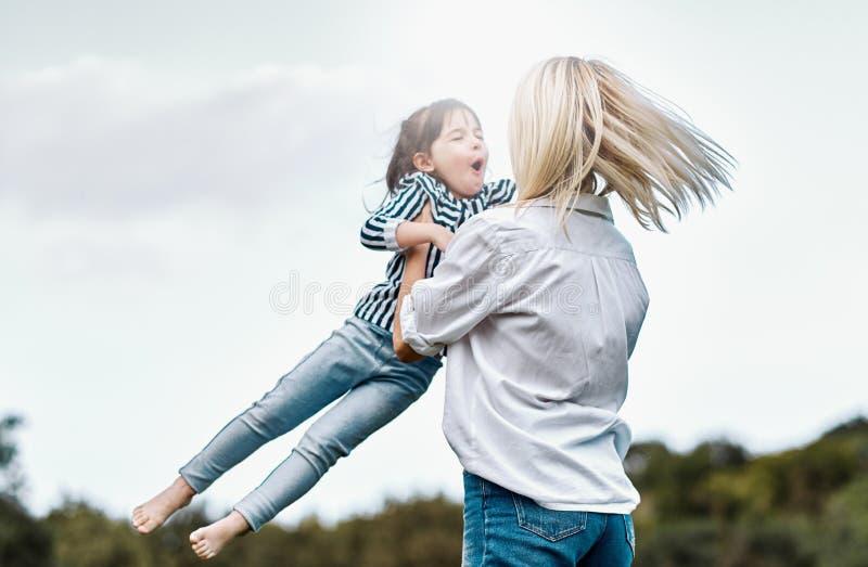 Imagen del aire libre de la pequeña hija feliz que juega con su madre sonriente en el parque Mujer de amor y su goce de la muchac imagenes de archivo