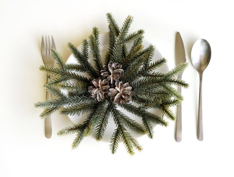 Imagen del ajuste de la tabla de las Navidades, placa festiva blanca con el cuchillo y bifurcación, decoración de plata brillante imagen de archivo libre de regalías