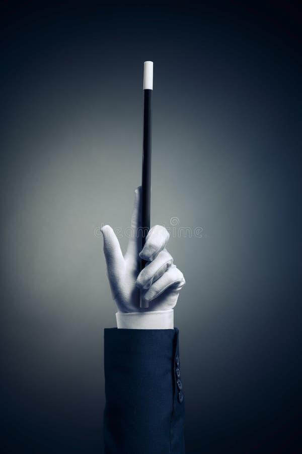 Imagen del alto contraste de la mano del mago con la vara mágica foto de archivo libre de regalías
