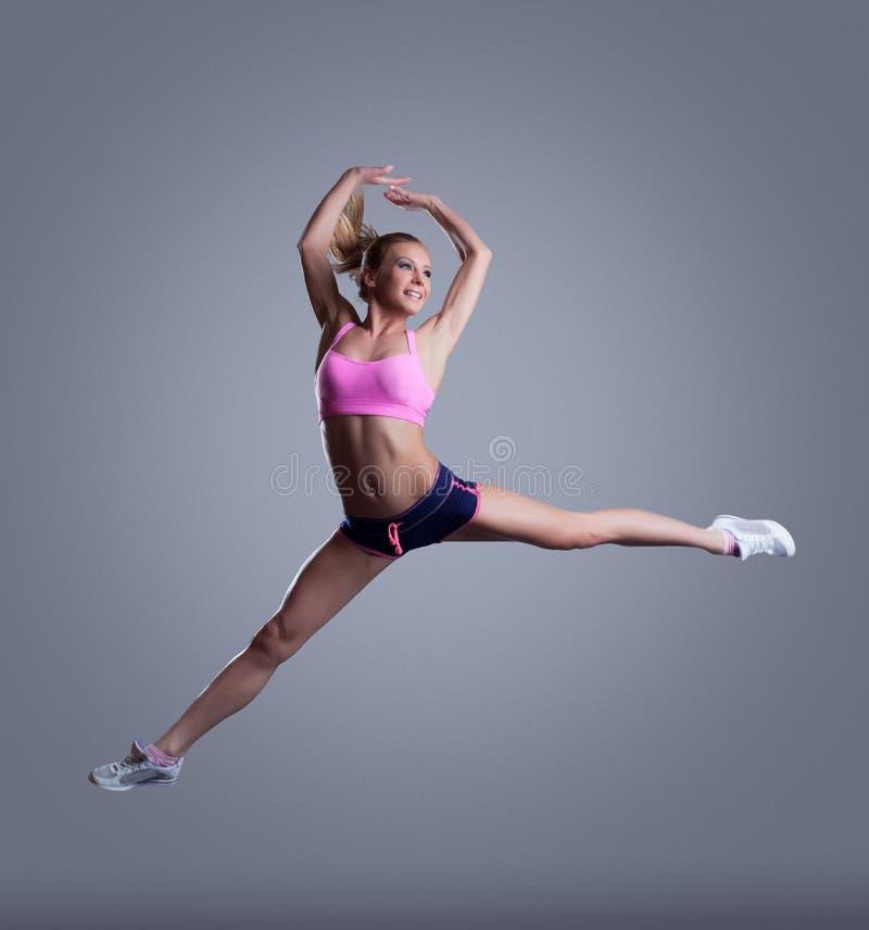 Imagen del atleta de sexo femenino joven feliz que presenta en salto imagen de archivo