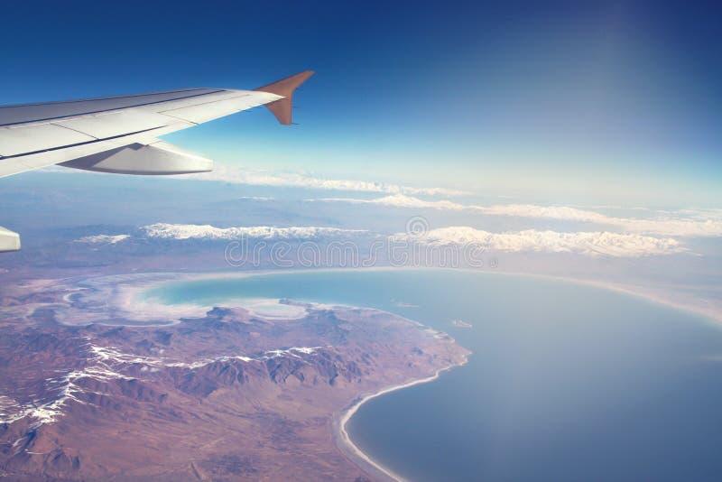 Imagen del avión y del ala con el mar, las montañas, y la costa costa Línea y salida del sol de Horizont imagen de archivo