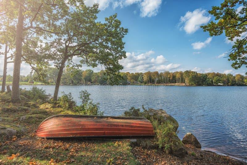 Imagen del barco de madera rojo en el día soleado del otoño con el lago azul en el fondo fotos de archivo