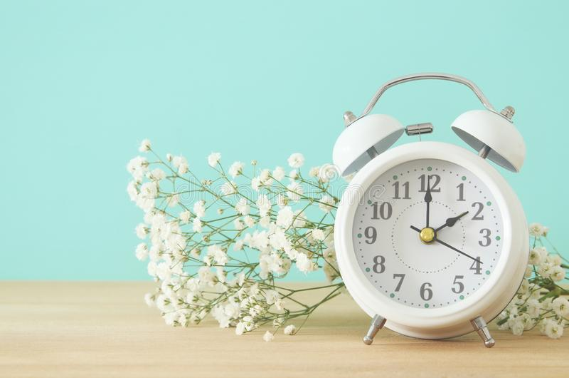Imagen del cambio del tiempo de primavera Concepto trasero del verano Despertador del vintage sobre la tabla de madera foto de archivo libre de regalías