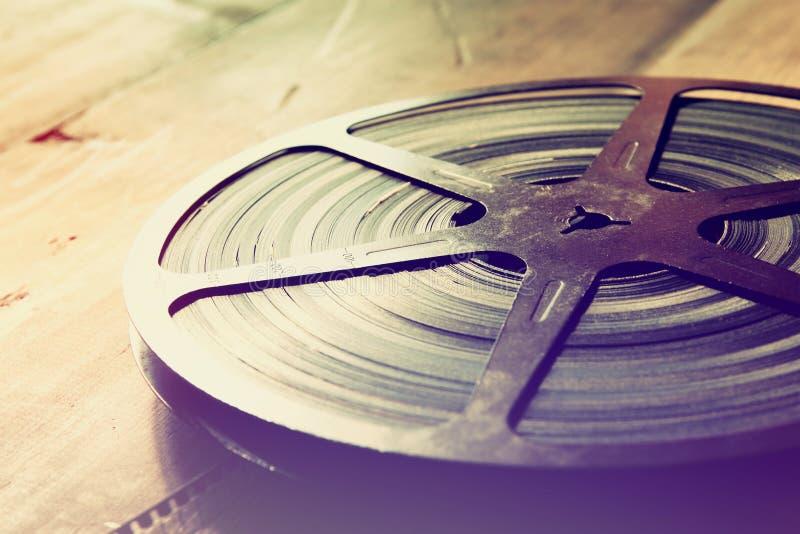 Imagen del carrete viejo de la película de 8 milímetros sobre fondo de madera Imagen retra del estilo foto de archivo