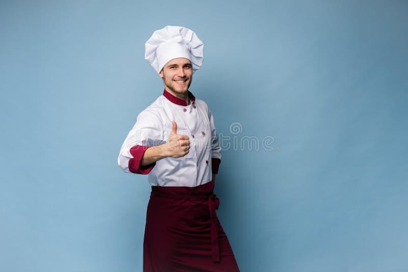 Imagen del cocinero joven feliz en pulgares que muestran uniformes para arriba fotografía de archivo libre de regalías