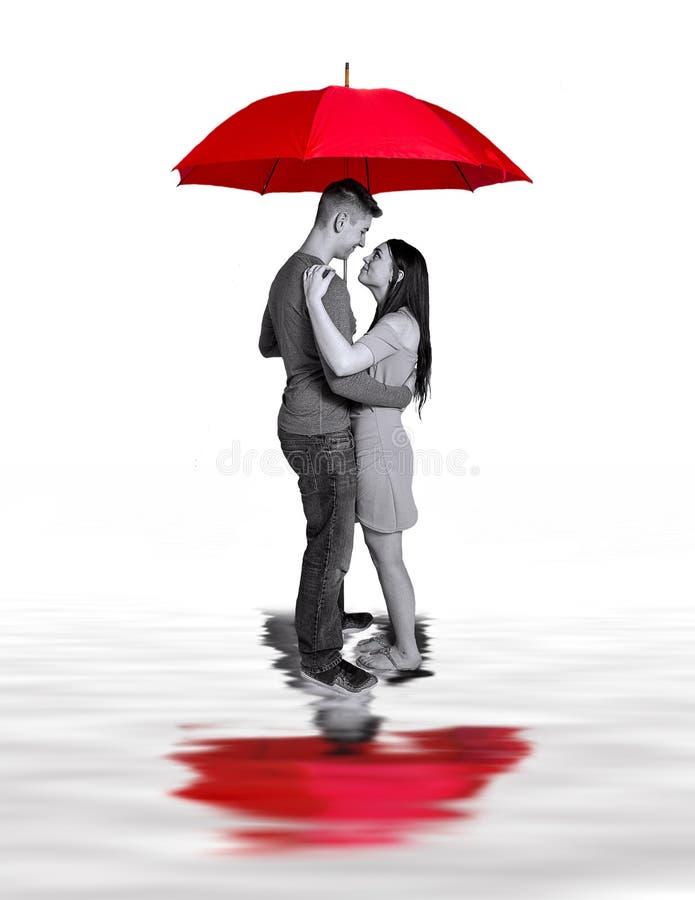 Imagen del concepto de pares en el amor que se coloca bajo el paraguas rojo grande y reflexiones en charcos Aislado en blanco foto de archivo libre de regalías