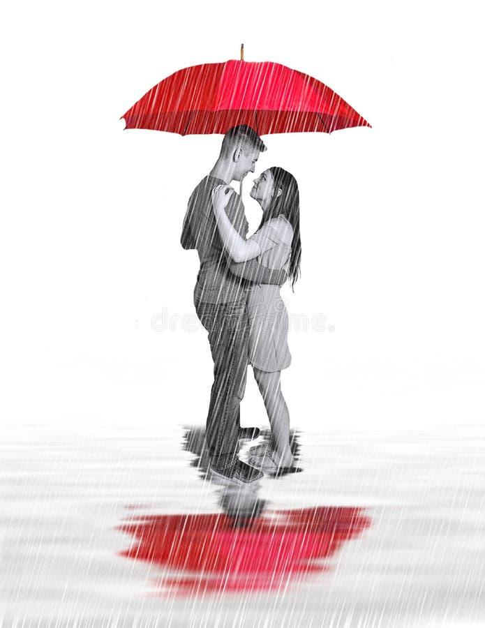 Imagen del concepto de pares en el amor que se coloca debajo del paraguas rojo grande mientras que llueve y reflexión en charcos  fotografía de archivo