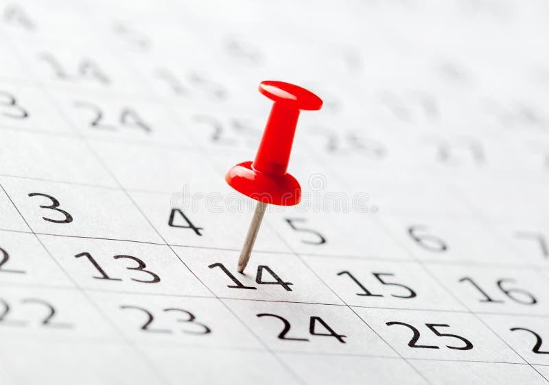 Imagen del concepto de un calendario con los pernos rojos del empuje foto de archivo libre de regalías