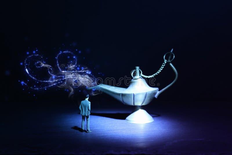 Imagen del concepto de un hombre de negocios que mira la l?mpara de Aladdin que pide un deseo imagen de archivo