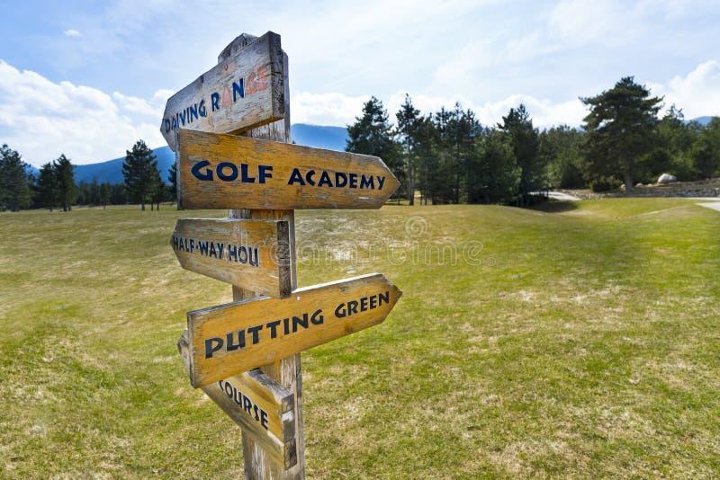 Imagen del concepto de un poste indicador con el campo de golf fotos de archivo