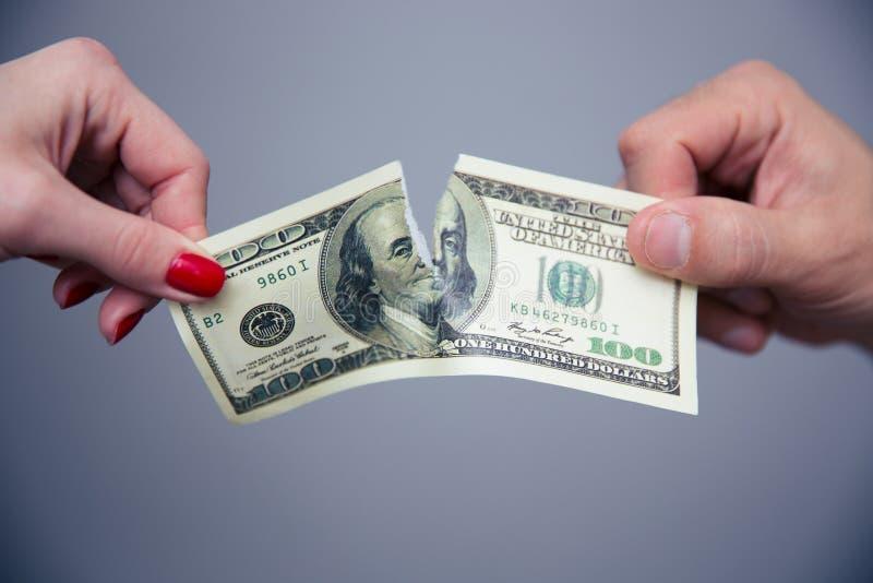 Imagen del concepto de una mano femenina y masculina que divide el dinero foto de archivo
