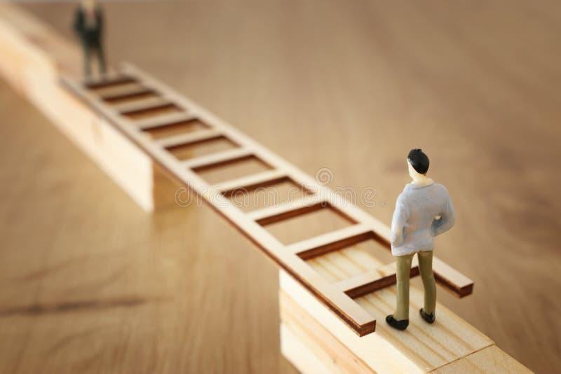 Imagen del concepto del negocio del desafío Un hombre se coloca al borde de una alta pared y pasa el hueco colocando una escalera imagen de archivo
