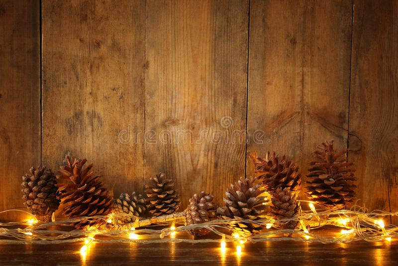 Imagen del día de fiesta con las luces de la guirnalda de la Navidad y los conos de oro del pino sobre fondo de madera imagen de archivo