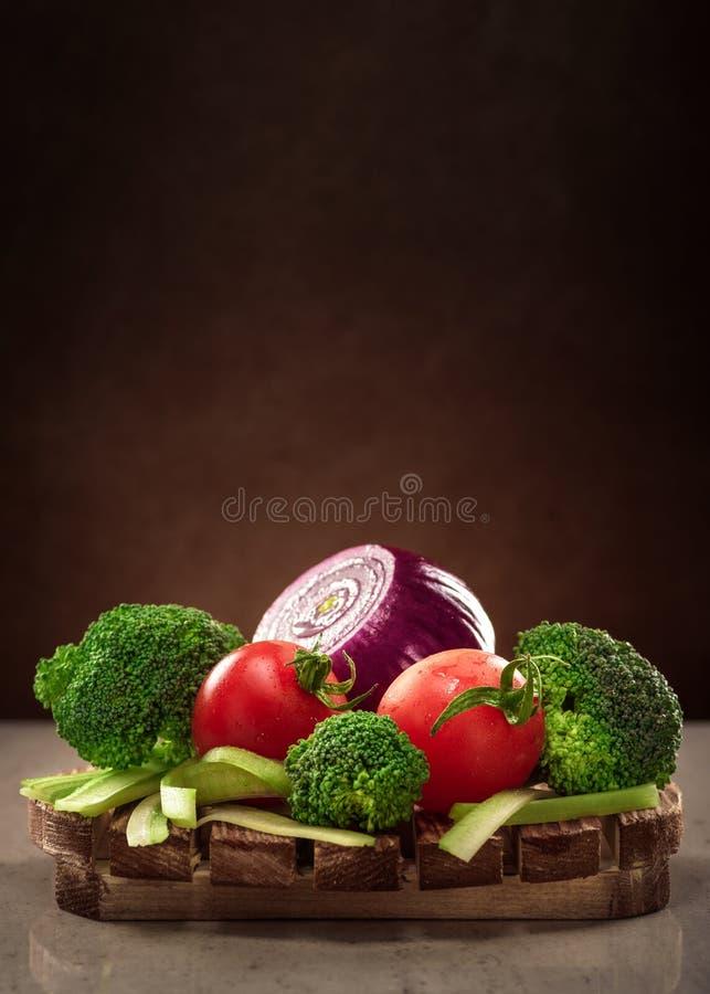 Imagen del diseño de concepto para un libro de cocina o las verduras de la portada de revista en un disco de madera en fondo oscu fotos de archivo libres de regalías