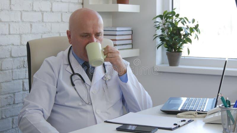 Imagen del doctor haciendo una pausa relajada y tomando una copa con té imágenes de archivo libres de regalías