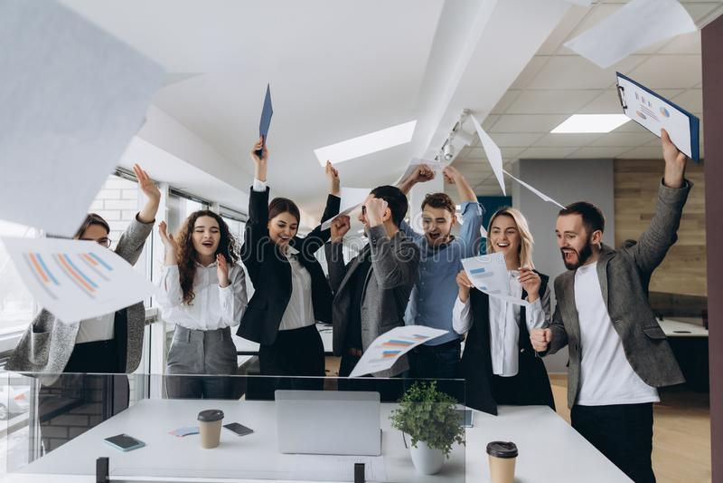 Imagen del equipo feliz del negocio que celebra la victoria en oficina El equipo acertado del negocio lanza trozos de papel en of imagenes de archivo