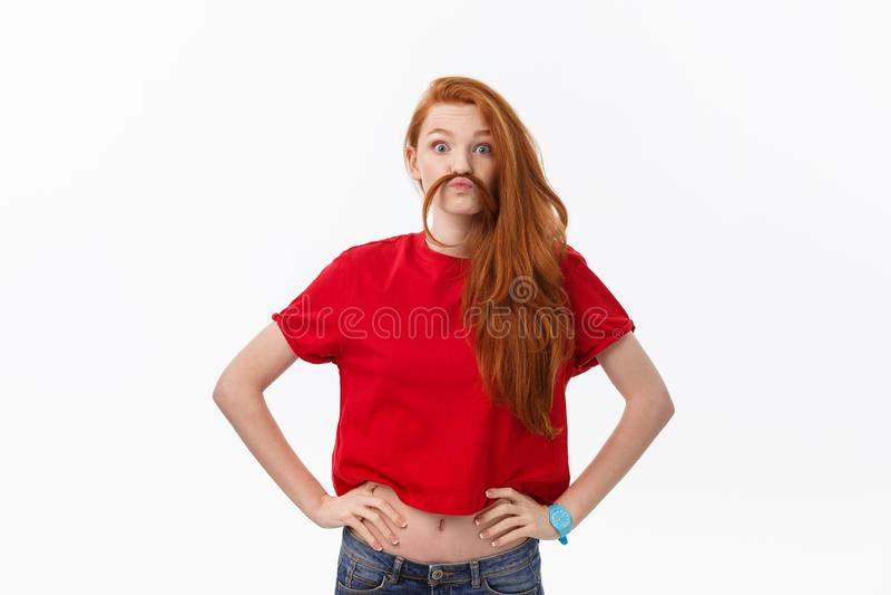 Imagen del estudio de la mujer alegre que juega con el pelo que sonríe y que ríe, presentando sobre el fondo blanco imagen de archivo libre de regalías