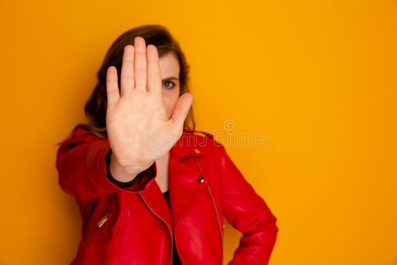 Imagen del getsure de la parada de la demostración de la mujer por su mano en un bacckground amarillo imágenes de archivo libres de regalías