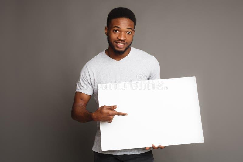 Imagen del hombre afroamericano joven que lleva a cabo al tablero en blanco blanco fotos de archivo