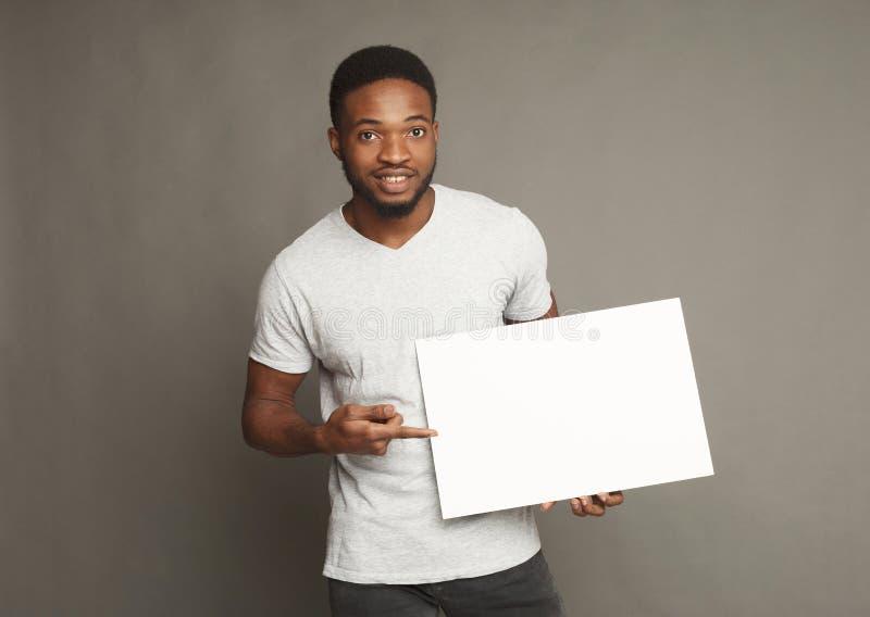 Imagen del hombre afroamericano joven que lleva a cabo al tablero en blanco blanco foto de archivo libre de regalías
