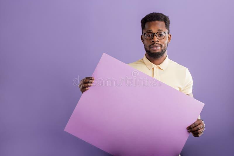 Imagen del hombre afroamericano joven que lleva a cabo al tablero en blanco en el fondo violeta foto de archivo libre de regalías