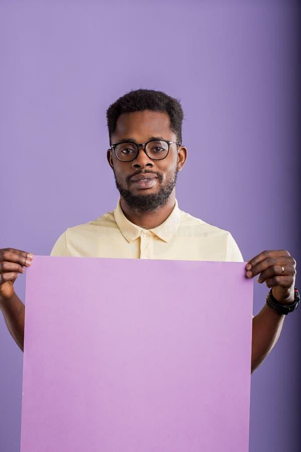 Imagen del hombre afroamericano joven que lleva a cabo al tablero en blanco en el fondo violeta imagen de archivo