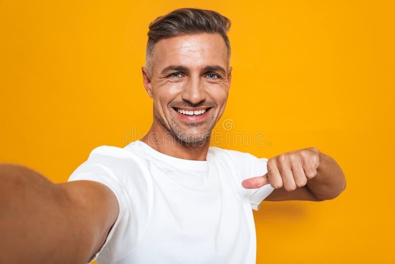 Imagen del hombre barbudo 30s en la camiseta blanca que sonríe y que toma la foto del selfie foto de archivo libre de regalías