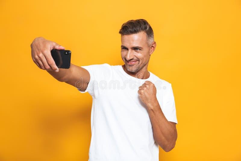 Imagen del hombre caucásico 30s en la camiseta blanca que gesticula y que toma la foto del selfie en el teléfono móvil fotos de archivo libres de regalías