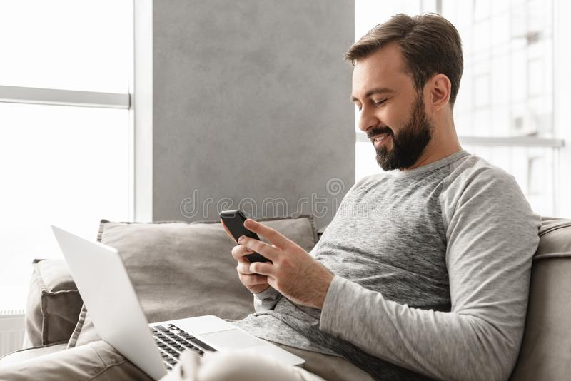 Imagen del hombre caucásico 30s en la ropa de sport que se sienta en el sofá en liv fotos de archivo libres de regalías