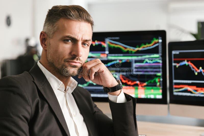 Imagen del hombre de negocios acertado que trabaja en oficina en el ordenador con los gráficos y las cartas en la pantalla fotografía de archivo