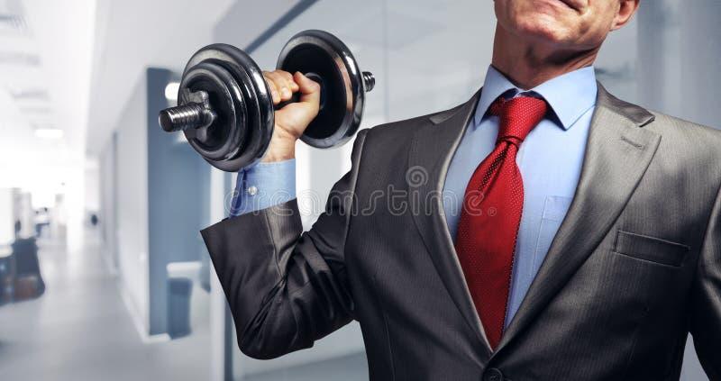 Imagen del hombre de negocios en el traje que aumenta pesa de gimnasia Concep de la presión fiscal fotos de archivo libres de regalías