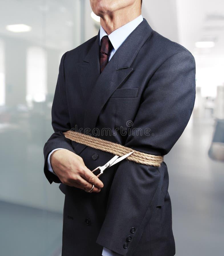 Imagen del hombre de negocios que intenta librarse de los grilletes imagen de archivo