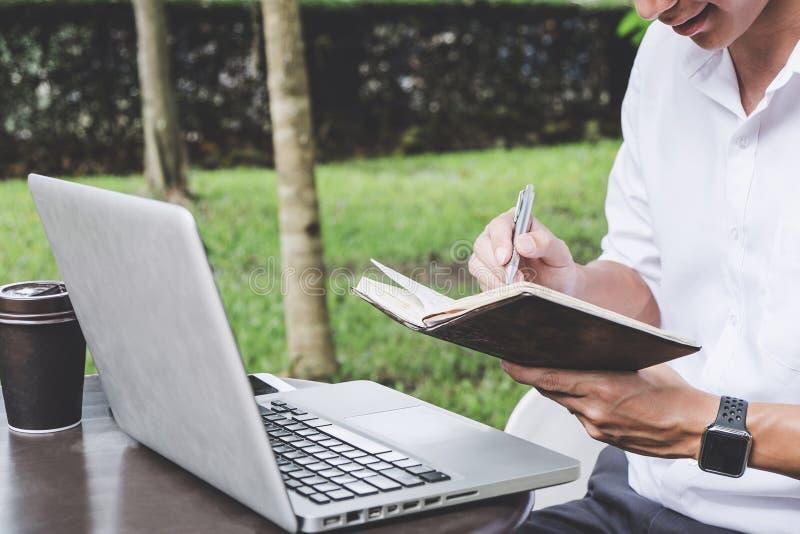 Imagen del hombre de negocios que trabaja con el ordenador portátil y los datos financieros sobre la tabla en oficina al aire lib foto de archivo