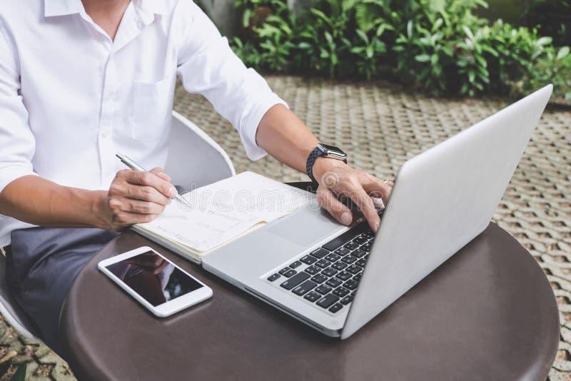 Imagen del hombre de negocios que trabaja con el ordenador port?til y los datos financieros sobre la tabla en oficina al aire lib fotografía de archivo