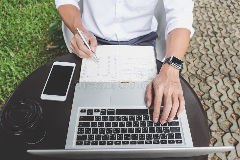 Imagen del hombre de negocios que trabaja con el ordenador port?til y los datos financieros sobre la tabla en oficina al aire lib imágenes de archivo libres de regalías