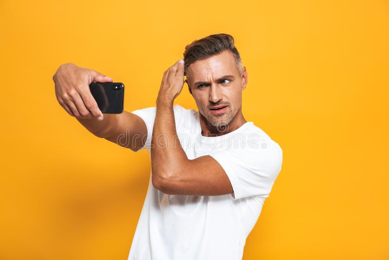 Imagen del hombre hermoso 30s en la camiseta blanca que gesticula y que toma la foto del selfie en el teléfono móvil fotografía de archivo libre de regalías