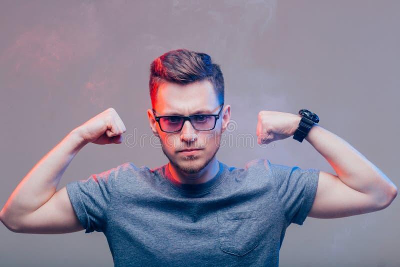 Imagen del hombre joven atractivo que muestra su bíceps imagen de archivo