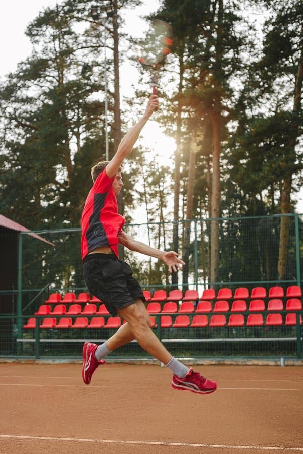 Imagen del hombre joven hermoso en campo de tenis Hombre que juega a tenis Pelota de tenis del hombre que lanza Área hermosa del  foto de archivo